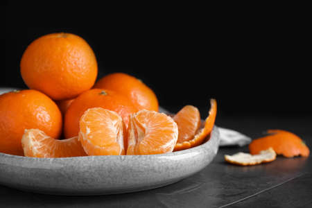 Delicious fresh ripe tangerines on black table