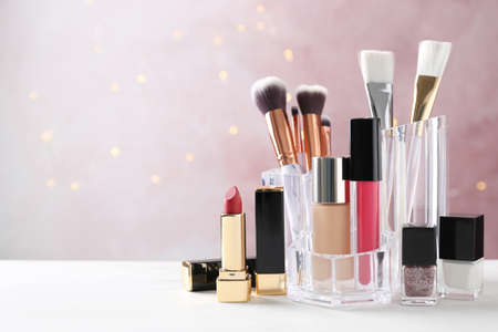 Makeup cosmetic products on white wooden table against pink background, space for text