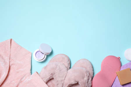 Flat lay composition with bathrobe, slippers and accessories on light blue background. Space for text Reklamní fotografie