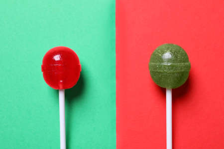 Two lollipops on color background, flat lay