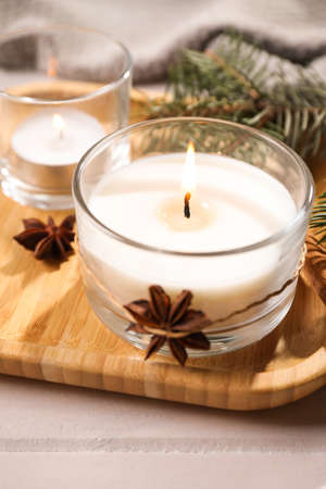 Decorated scented candles in glass holders on wooden tray