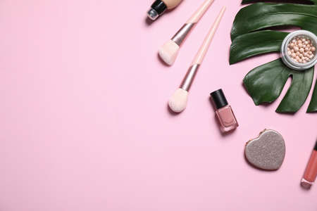 Makeup products and green leaf on pink background, flat lay. Space for text