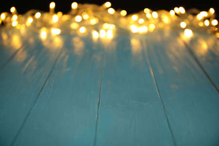 Blurred view of beautiful glowing lights, focus on light blue wooden table. Space for text
