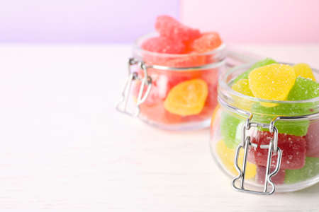Yummy candies in glass jars on white table, space for text