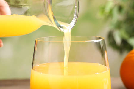 Pouring fresh orange juice into glass, closeup