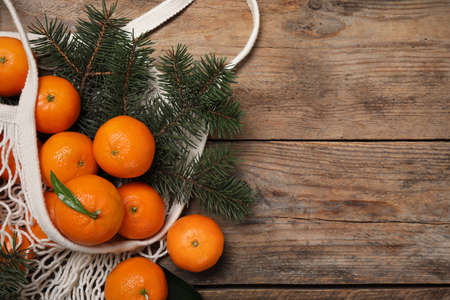 Fresh ripe tangerines, fir tree branches and mesh bag on wooden table, flat lay. Space for text Reklamní fotografie