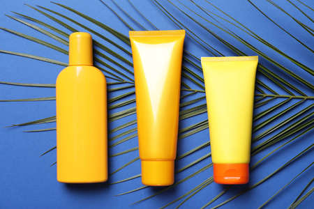 Different sun protection cosmetic products and green palm leaf on blue background, flat lay