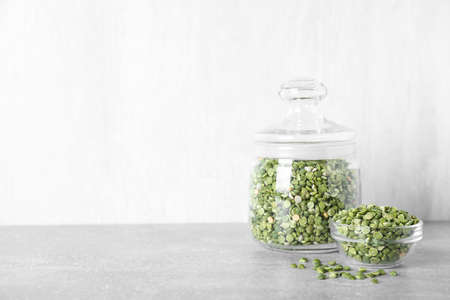 Dried peas in glass jar on grey table, space for text