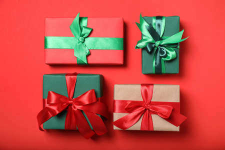 Elegant gift boxes with bows on red background, flat lay