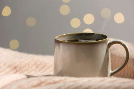 Cup of hot drink on pink sweater against blurred lights, closeup. Cozy atmosphere