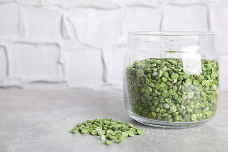 Glass jar with dry green peas on light grey table. Space for text Reklamní fotografie