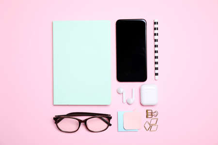 Flat lay composition with smartphone and stationery on pink background