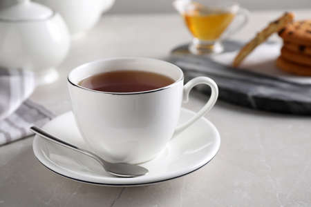 Cup of hot tea and spoon on light grey table