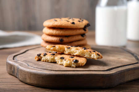 Delicious cookies with chocolate on wooden board