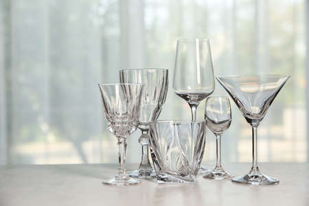 Different elegant empty glasses on grey table indoors Фото со стока