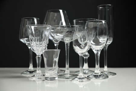 Set of bar glassware on white table against black background Фото со стока