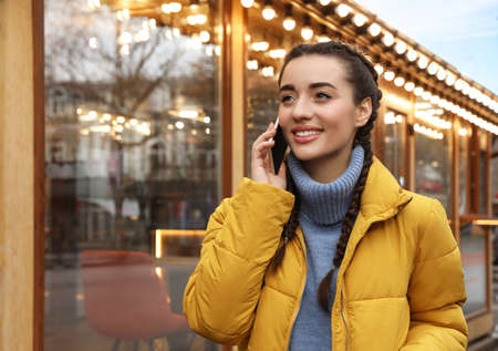 Young woman talking on mobile phone near cafe decorated for Christmas
