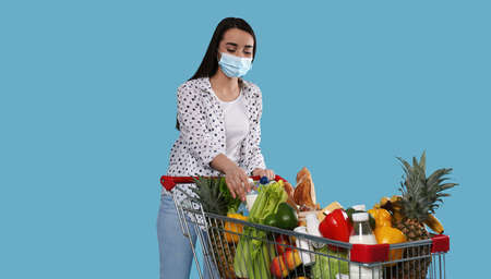 Young woman in medical mask with shopping cart full of groceries on light blue background 版權商用圖片
