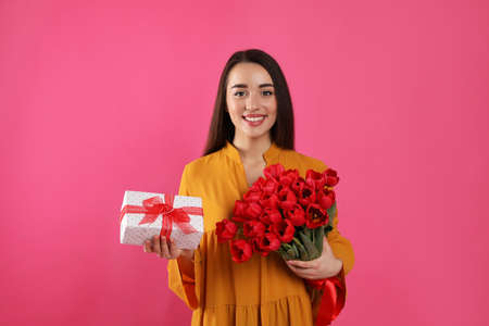 Happy woman with red tulip bouquet and gift box on pink background. 8th of March celebration 版權商用圖片