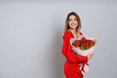 Happy woman with red tulip bouquet on light grey background, space for text. 8th of March celebration