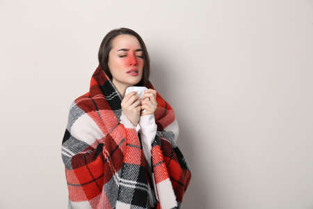 Young woman with blanket sneezing on light background, space for text. Runny nose