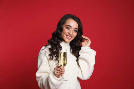 Beautiful young woman in warm sweater holding glass of champagne on red background. Christmas party