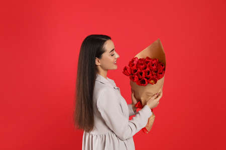 Happy woman with tulip bouquet on red background. 8th of March celebration 版權商用圖片