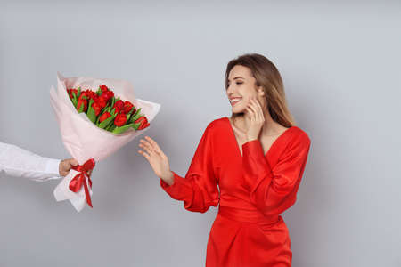 Happy woman receiving red tulip bouquet from man on light grey background. 8th of March celebration