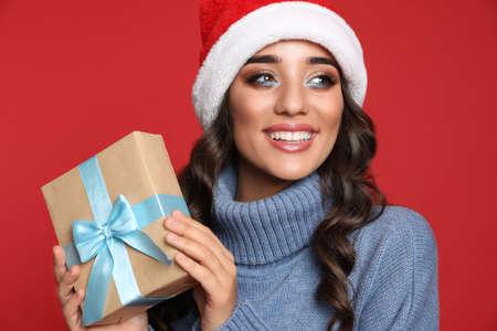 Beautiful woman in Santa hat with Christmas gift on red background