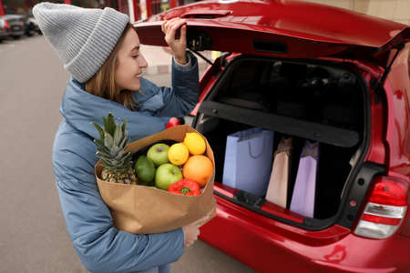 Young woman with bag of groceries near her car outdoors