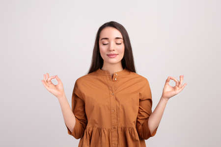 Young woman meditating on beige background. Stress relief exercise