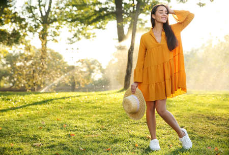 Beautiful young woman wearing stylish yellow dress with straw hat in park