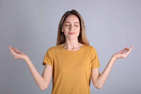 Young woman meditating on grey background. Stress relief exercise 版權商用圖片