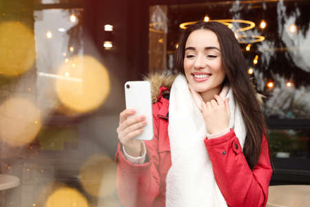 Young woman taking selfie at winter fair. Christmas celebration