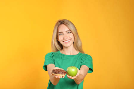 Woman choosing between doughnut and healthy apple on yellow background