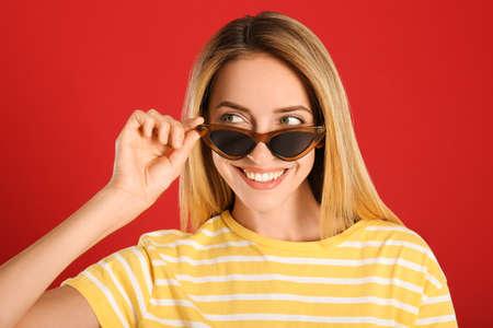Beautiful woman in stylish sunglasses on red background 版權商用圖片