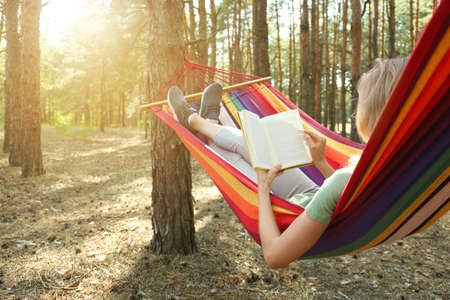 Woman with book relaxing in hammock outdoors on summer day