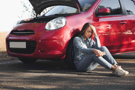 Stressed woman with smartphone near broken car outdoors