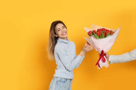 Happy woman receiving red tulip bouquet from man on yellow background. 8th of March celebration