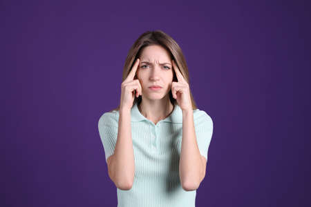 Portrait of stressed young woman on purple background