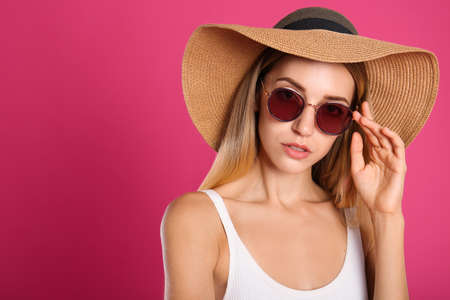 Beautiful woman in stylish sunglasses on pink background. Space for text