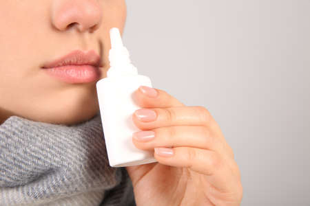 Woman using nasal spray on light grey background, closeup. Space for text 版權商用圖片