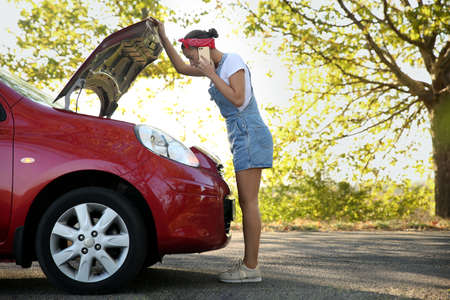 Stressed woman talking on phone near broken car outdoors 版權商用圖片