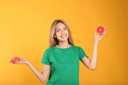 Woman choosing between doughnut and healthy grapefruit on yellow background 版權商用圖片