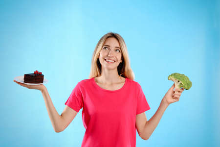 Woman choosing between cake and healthy broccoli on light blue background