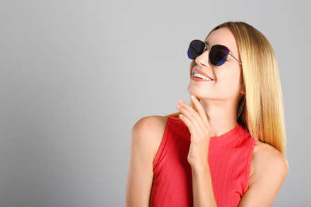 Beautiful woman in stylish sunglasses on grey background. Space for text 版權商用圖片