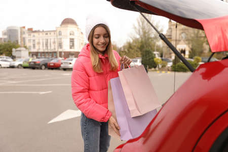 Woman with shopping bags near her car outdoors