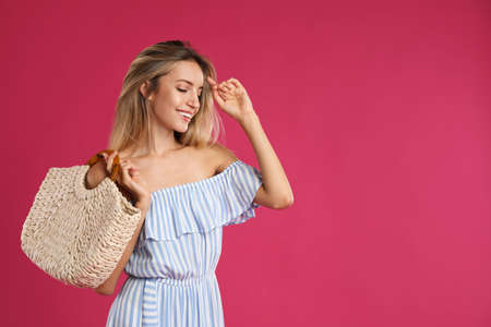 Beautiful young woman with stylish straw bag on pink background. Space for text