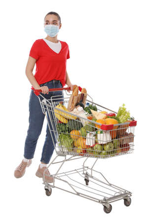 Woman with protective mask and shopping cart full of groceries on white background