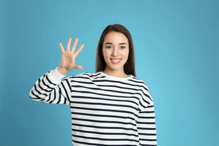 Woman showing number five with her hand on light blue background 版權商用圖片